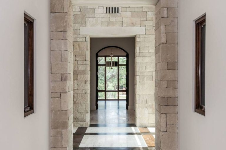 white stone hallway with windows at the end